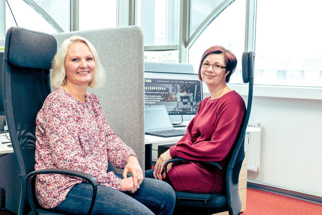 Erpistit Navakan toimistolla. Kuvassa Karmila ja Katja työpisteillään.